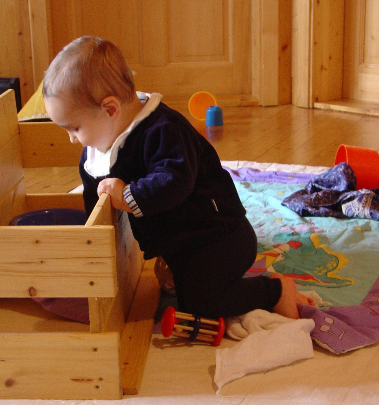 Baby zieht sich hoch und sitzt angelehnt auf den Knien.